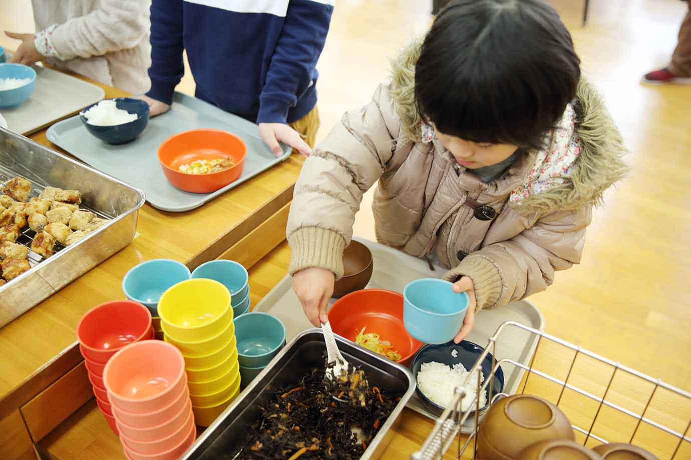 小学校1年生の児童も、好きな器を選び、食べられる量を考えながら盛り付ける