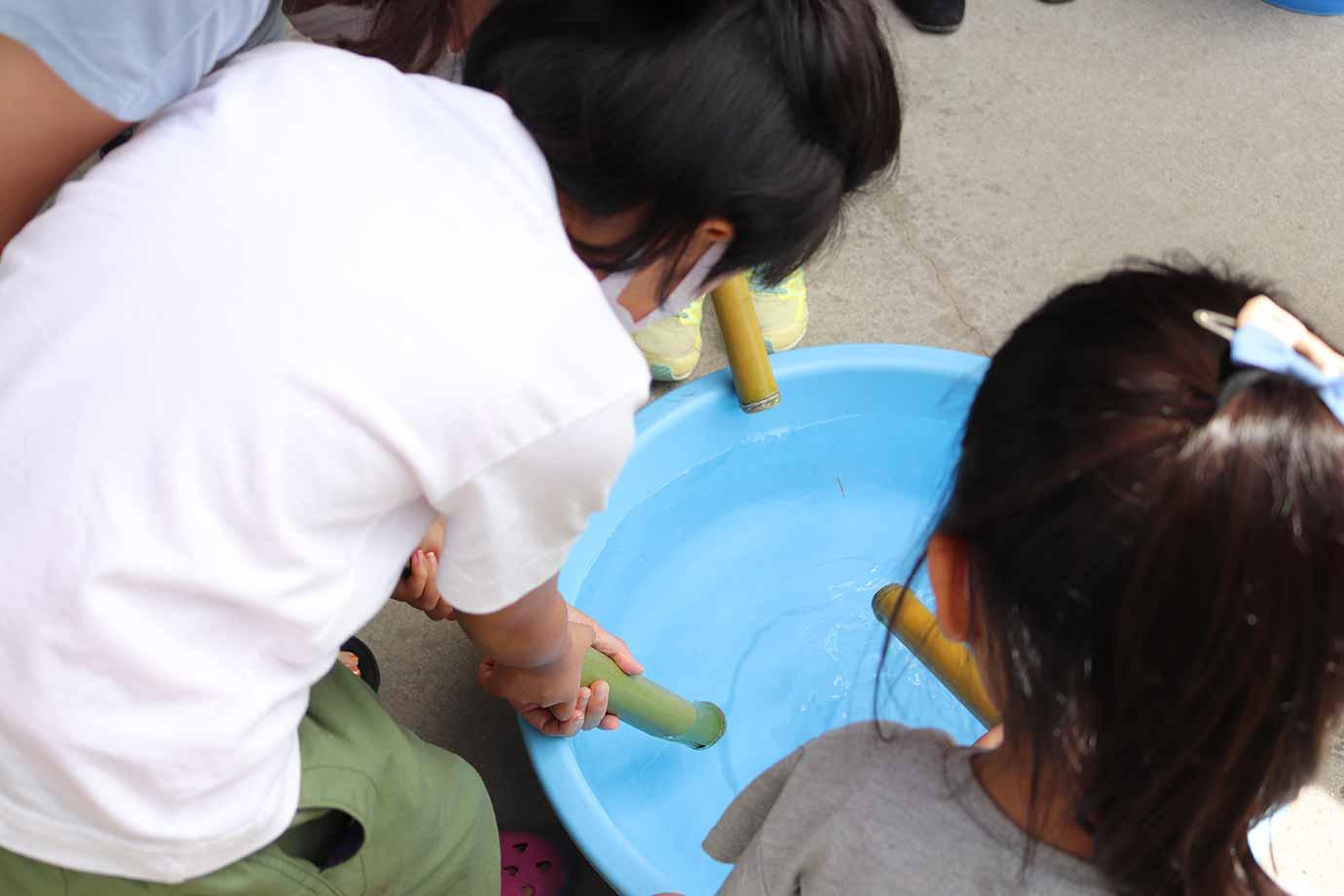 水の入った桶から、水鉄砲に給水します。