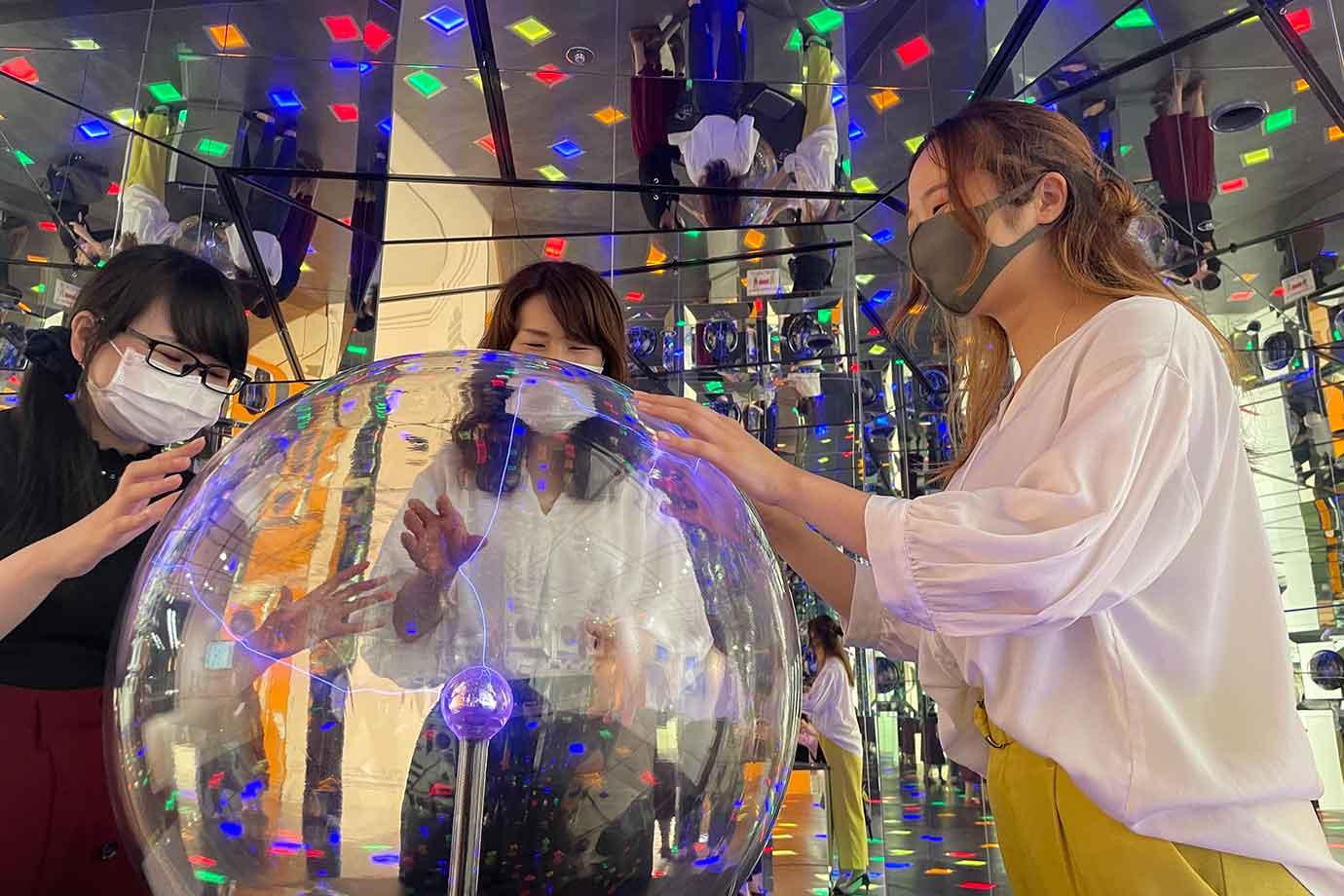 鏡が張り廻らされた空間の真ん中には、透明なプラズマボールが置かれており、手を触れると光の筋が集まります